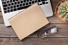 Table de bureau avec l'ordinateur portable, le bloc-notes et les verres Images stock