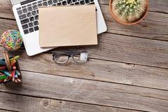 Table de bureau avec l'ordinateur portable, le bloc-notes et les verres Photographie stock libre de droits