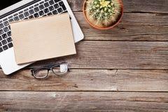 Table de bureau avec l'ordinateur portable, le bloc-notes et les verres Photo stock