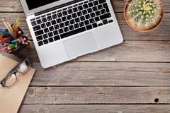 Table de bureau avec l'ordinateur portable, le bloc-notes et les verres Image stock