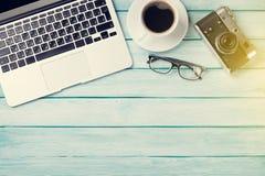 Table de bureau avec l'ordinateur portable, le café et l'appareil-photo Photos libres de droits