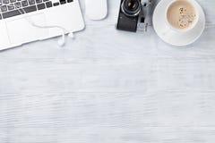 Table de bureau avec l'ordinateur portable, le café et l'appareil-photo Photographie stock