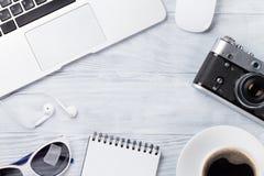 Table de bureau avec l'ordinateur portable, le café et l'appareil-photo Image libre de droits