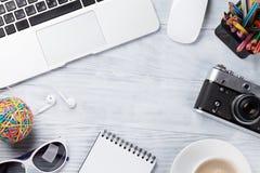 Table de bureau avec l'ordinateur portable, le café et l'appareil-photo Photo stock