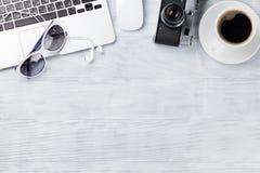Table de bureau avec l'ordinateur portable, le café et l'appareil-photo Photo libre de droits