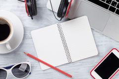 Table de bureau avec l'ordinateur portable, le café et le bloc-notes Image stock