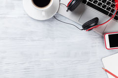 Table de bureau avec l'ordinateur portable, le café et les écouteurs Photos stock