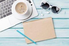 Table de bureau avec l'ordinateur portable, le café et les lunettes de soleil Photographie stock