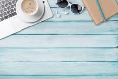 Table de bureau avec l'ordinateur portable, le café et les lunettes de soleil Image libre de droits