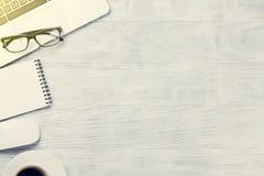 Table de bureau avec l'ordinateur portable, le café et les verres Photo libre de droits