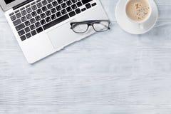 Table de bureau avec l'ordinateur portable, le café et les verres Photos libres de droits