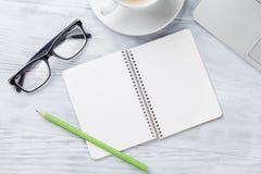 Table de bureau avec l'ordinateur portable, le café, le bloc-notes et les verres Photo stock