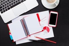 Table de bureau avec l'ordinateur portable, le café, le smartphone et les rapports Photographie stock