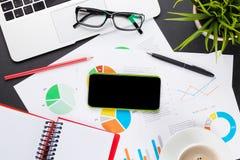 Table de bureau avec l'ordinateur portable, le café, le smartphone et les rapports Photos libres de droits