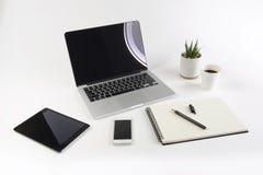 Table de bureau avec l'ordinateur portable, le carnet, le comprimé numérique et le smartphone sur le fond blanc Image stock