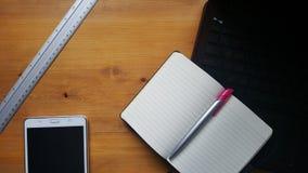 Table de bureau avec l'ordinateur portable, le comprimé, la règle et le carnet Photographie stock libre de droits