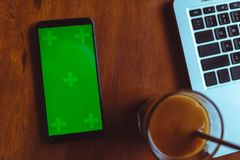 Table de bureau avec l'ordinateur portable, le smartphone avec l'écran vert et le café Images libres de droits
