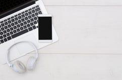 Table de bureau avec l'ordinateur portable, le smartphone, et les écouteurs images libres de droits