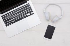Table de bureau avec l'ordinateur portable, le smartphone, et les écouteurs photographie stock