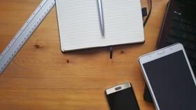 Table de bureau avec l'ordinateur portable, le téléphone, la règle et le carnet Image stock