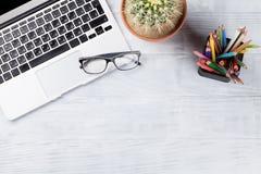 Table de bureau avec l'ordinateur portable, les verres et les crayons Images libres de droits