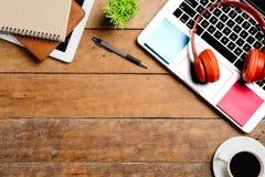 Table de bureau avec l'ordinateur portable, téléphone intelligent, stylo, écouteur Image stock
