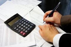 Table de bureau avec la calculatrice, le stylo et le document comptable photos libres de droits