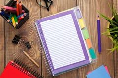 Table de bureau avec la fleur, le bloc-notes vide et les crayons colorés Image libre de droits