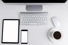 Table de bureau avec la tablette et le smartphone, le clavier d'ordinateur sans fil et la souris, tasse de café, carnet de l'espa Photo libre de droits