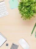 Table de bureau avec le bloc-notes, l'ordinateur et la fleur Image libre de droits