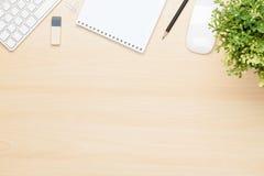 Table de bureau avec le bloc-notes, l'ordinateur et la fleur Photographie stock libre de droits