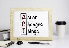 Table de bureau avec le cadre en bois avec le texte - l'action change des choses Image stock