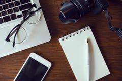 Table de bureau avec le carnet et l'ordinateur portable vides Photo stock