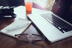 Table de bureau avec le carnet et l'ordinateur portable vides Photos stock
