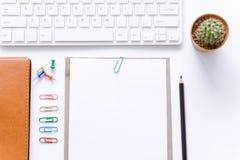 Table de bureau avec le clavier d'ordinateur, fournitures de bureau sur le fond blanc Photographie stock libre de droits