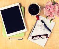 Table de bureau avec le comprimé numérique, la tasse en verre de lecture de café et le bloc-notes Vue de ci-avant Image stock
