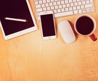 Table de bureau avec le comprimé numérique, le smartphone et la tasse de café Vue de ci-avant Photographie stock libre de droits