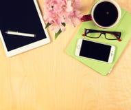 Table de bureau avec le comprimé numérique, le smartphone, les verres de lecture et la tasse de café Vue de ci-avant Image stock