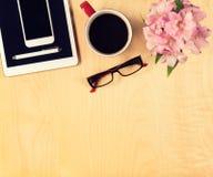 Table de bureau avec le comprimé numérique, le smartphone, les verres de lecture et la tasse de café Vue de ci-avant Photo stock