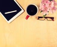 Table de bureau avec le comprimé numérique, les verres de lecture et la tasse de café Vue de ci-avant Photo libre de droits
