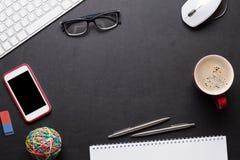 Table de bureau avec le PC, le bloc-notes, les verres, le café et le téléphone Image stock