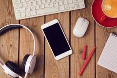 Table de bureau avec le smartphone et les écouteurs Concept de lieu de travail ou d'espace de travail d'affaires Photos stock