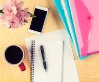 Table de bureau avec le smartphone, la feuille de papier vide, les dossiers remplissants et la tasse de café Vue de ci-avant Photo stock
