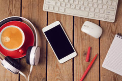 Table de bureau avec le smartphone, les écouteurs et la tasse de café Concept de lieu de travail ou d'espace de travail d'affaire Photo libre de droits