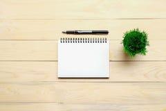 Table de bureau avec le stylo, le carnet et la fleur Image libre de droits