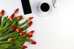 Table de bureau avec le téléphone portable, le carnet de papier, la tasse de café et le beau groupe frais de tulipes de fleurs Photo libre de droits