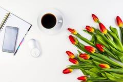 Table de bureau avec le téléphone portable, le carnet de papier, la tasse de café et le beau groupe frais de tulipes de fleurs Images libres de droits