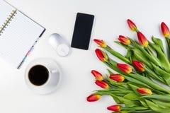 Table de bureau avec le téléphone portable, le carnet de papier, la tasse de café et le beau groupe frais de tulipes de fleurs Images stock