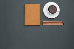 Table de bureau avec les crayons, le carnet et une tasse de café Photographie stock libre de droits