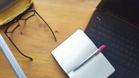 Table de bureau avec les verres, l'ordinateur portable, le téléphone, le carnet et la règle Photos stock